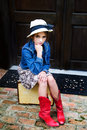 Ready to travel young girl sitting on a vintage suit case wearing a hat and red boots Stock Photography