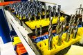 stock image of  Ready twist drills made from metal base bars on yellow plastic support. Horizontal, tools and instruments