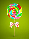 Reainbow lollipop with bow on green background d Stock Photography