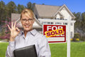Real estate agent in front of sold sign and house female home for sale Stock Images
