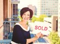 Real estate agent holding sold sign on city background positive face expression Royalty Free Stock Photo
