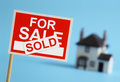 Real estate agent for sale sign with sold label and house in background Stock Photography