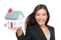 Real estate agent selling home holding mini house female realtor in business suit showing model smiling happy isolated on Royalty Free Stock Photos