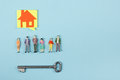 Real Estate concept. Blank speech bubbles and people toy figures Construction, building. Paper model house with key on Royalty Free Stock Photo