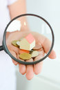 Real estate concept - coins and house architectural model in woman hand under magnifying glass Royalty Free Stock Photo