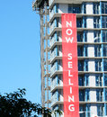 Real estate concrete highrise construction site now selling sign blue sky background Stock Images