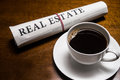 Real estate newspaper cup of coffee on desk Royalty Free Stock Image