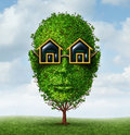 Real estate planning concept as a green tree shaped as a human head with eye glasses in the shape of a home or house as a symbol Stock Photography