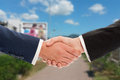 Real estate sale handshake over land and sky background Royalty Free Stock Photo