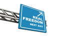 Real freedom words showing as next exit on a blue highway sign white background concept of personal in sense that is Royalty Free Stock Photography