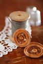Real old reels spoons treads with wood buttons on wooden table Stock Image