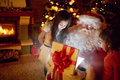 Real Santa Claus with children opening present with magical eff Royalty Free Stock Photo