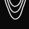 Realistic pearl necklace hangs on a dark background.