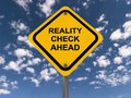 Reality check adhead yellow roadway style sign with text ahead in uppercase black letters blue sky and cloud background Stock Image