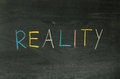 Reality word handwritten on the school blackboard Stock Images
