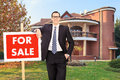 Realtor advertising a house for sale standing in the front yard outside Stock Photo