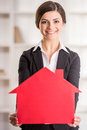 Realtor happy woman is showing home for sale sign Stock Images