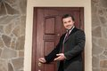 Realtor opening wooden door and smiling welcoming. Royalty Free Stock Photo