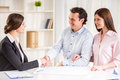 Realtor young couple signing financial contract with female Royalty Free Stock Photo