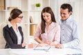 Realtor young explain lease agreement to young couple Stock Photos