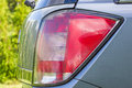 Rear car light detail of the end of a silver with focus on the brake lights Royalty Free Stock Photos