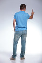 Rear of a casual man pressing an imaginary button back view young pushing on gray background Stock Image