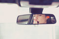 Rear mirror view of a sleepy yawning woman driving her car after long hour drive. Royalty Free Stock Photo