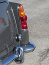 Rear of an old italian classic car . Particular view of right tail light and shiny chrome bumper Royalty Free Stock Photo