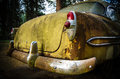 Rear of rusted old car end a yellow coupe from the s Stock Image