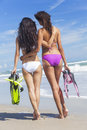 Rear view beautiful bikini women at beach of two young in bikinis with snorkel mask flippers embracing on a deserted with blue sky Royalty Free Stock Photography