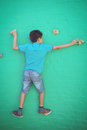 Rear view of boy climbing on green wall Royalty Free Stock Photo