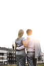 Rear view of business couple standing with arms around against clear sky on sunny day Royalty Free Stock Photo