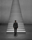 Rear view businessman climbing on stairs with spot lighting and concrete background Royalty Free Stock Photo