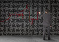 Rear view of a businessman drawing a red line through black maze on wall Stock Photo