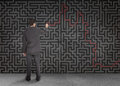 Rear view of a businessman writing a red line through black maze on wall Stock Photo