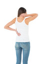 Rear view of a casual woman suffering from neck ache young over white background Stock Image