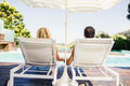 Rear view of couple on deck chairs poolside Stock Photos