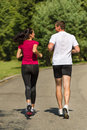Rear view of couple friends jogging together outdoors Royalty Free Stock Photos