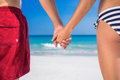 Rear view of couple holding hands at the beach on a sunny day Royalty Free Stock Images