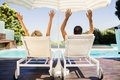 Rear view of couple raising hands and lying on deck chairs poolside Royalty Free Stock Photos