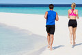 Rear view of couple running on beautiful beach happy Stock Images