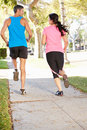 Rear view of couple running on suburban street away from camera Royalty Free Stock Image