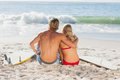 Rear view of a couple sitting on the beach and looking at the sea young Stock Photography