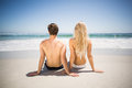 Rear view of couple sitting on the beach a sunny day Royalty Free Stock Images