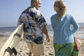 Rear view of a couple with surf boards on beach middle aged walking the Royalty Free Stock Image