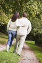 Rear view of couple walking along path Stock Image