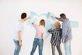 Rear view of couples painting wall in new home Royalty Free Stock Photo