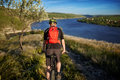 Rear view of the cyclist riding with mountain bike on the trail above river. Royalty Free Stock Photo