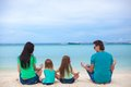 Rear view of a family of four sitting in the lotus position on beach this image has attached release Royalty Free Stock Image