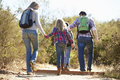 Rear view of family hiking in countryside wearing backpacks Stock Images